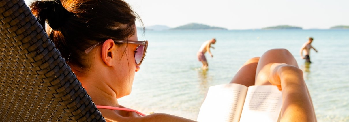 Woman on sun bed on the beach reading a book. People in background walking into sea.