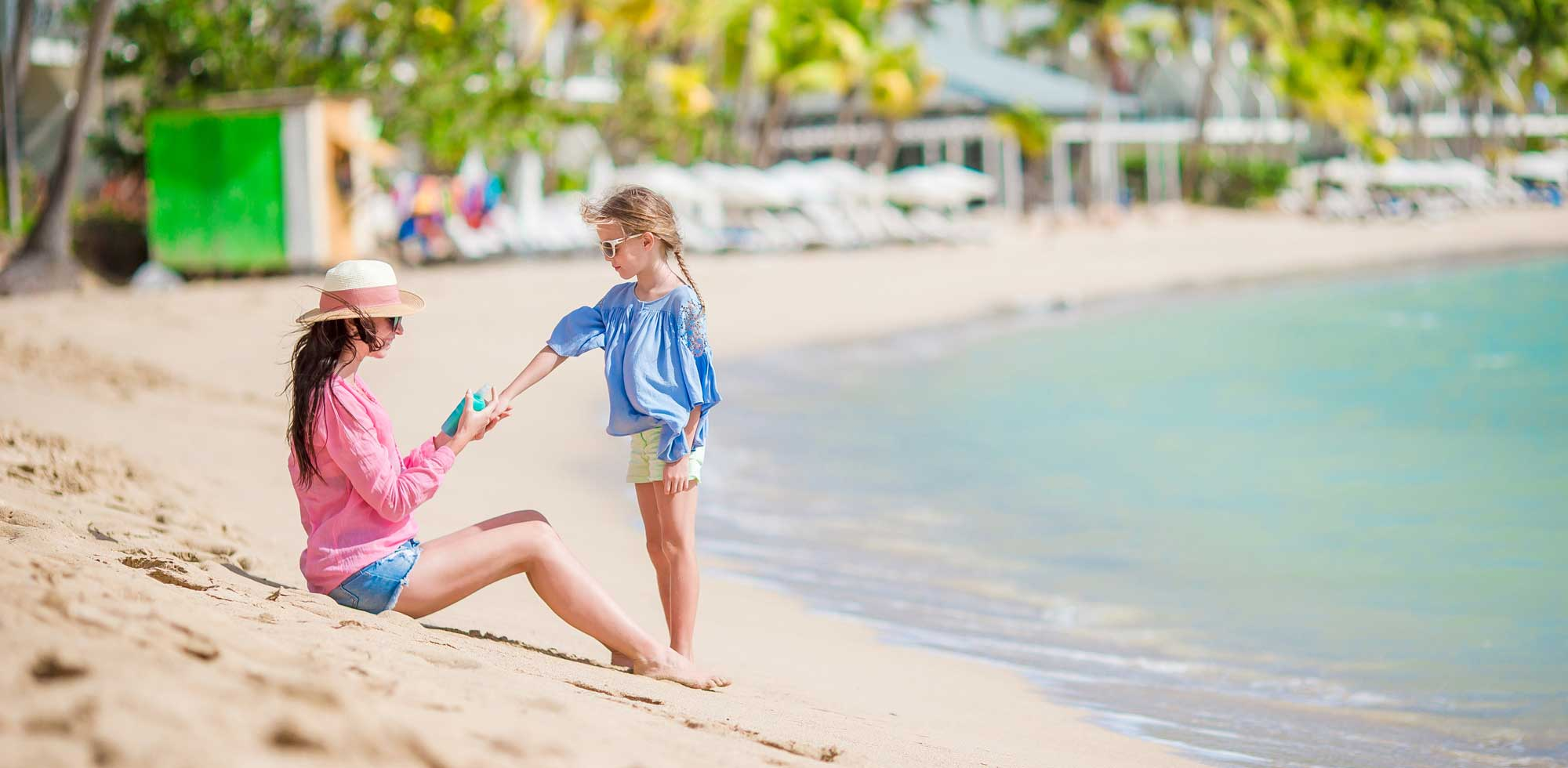 Young mother applying sunscreen on her daughter